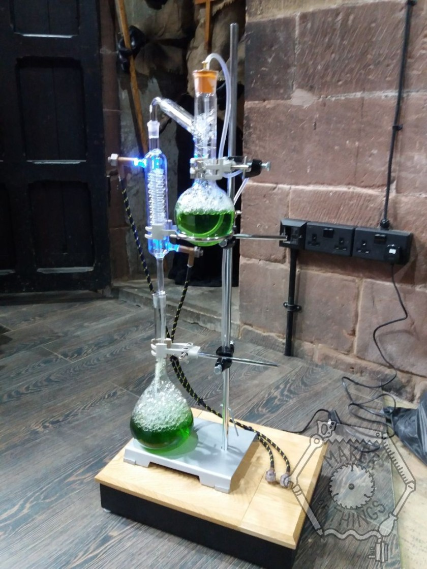 A view of the whole Mad Science prop delivered to site with the red stone walls of the ex church building in the background, showing the black and oak plinth, the laboratory stand green liquid in the top flask, green liquid in the bottom flask, and blue lighting in the condenser.