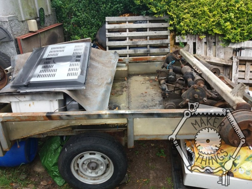 An open car trailer measuring 1700mm wide by 2000mm long and 300mm deep. There is a pile of scrap metal in the back of the trailer covered with a plastic sheet, and at the front of the trailer there is a caravan axle and the complete set of axles and suspension from an old Citroen 2CV car. IN the background is a hedge and some wooden pallets leaning against it.