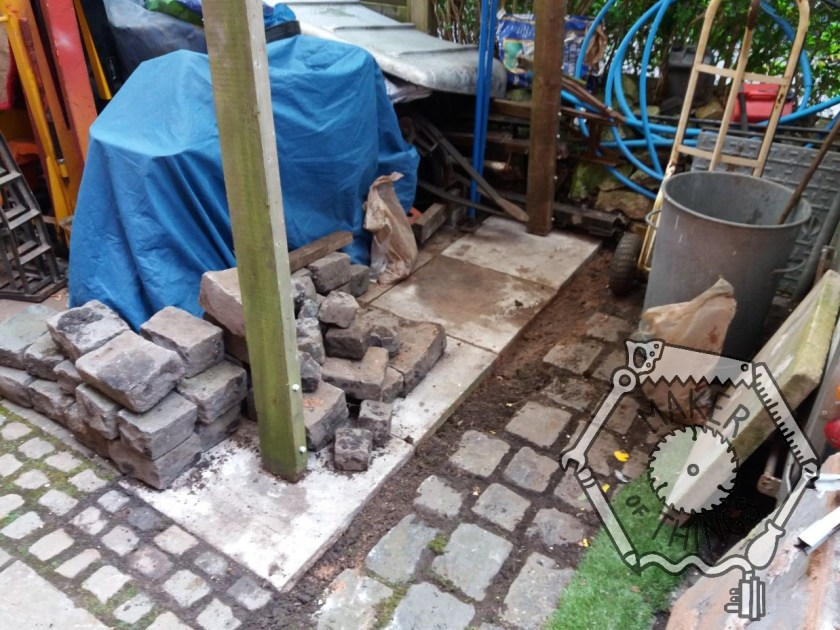 An overall view of the area previously laid with granite sets now with one rown of four concrete paving slabs in place. There is a large pile of granite sets piled onto the new slabs next to the mobility scooter under the bleet cover.