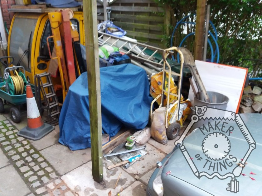 The space under the carport in front of the green Skoda estate car. There is a sack barrow, the blue covered mobility scooter, a folded engine crane, and the side view of Beryl's yellow cab.