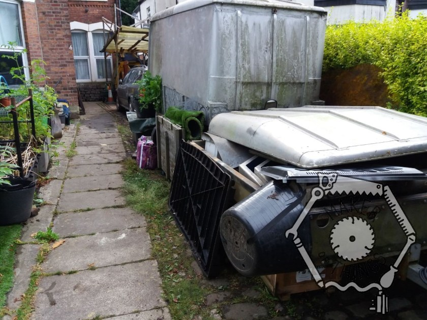 A view up the driveway showing an open trailer full of metal and a Land Rover roof on top, Behind is the big silver box trailer, then there is the green Skoda estate car, and the car port. There is a paved foot path to the left and a hedge on the right.