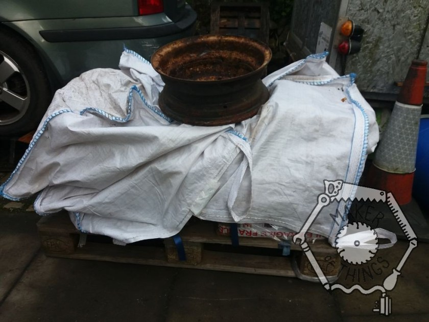 A pallet delivery of stuff, at the back of the car covered in white builder's bulk bags and weighted down with a rusty wheel.