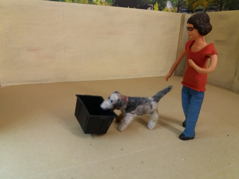 Harriet and Monty Dog are returning to the workshop. Monty is carrying the empty recycling box in his mouth.