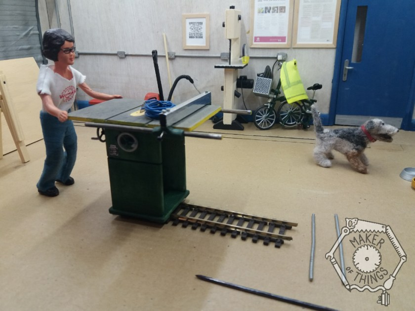 Harriet is pushing the table saw back along the railway track towards the big roller shutter.