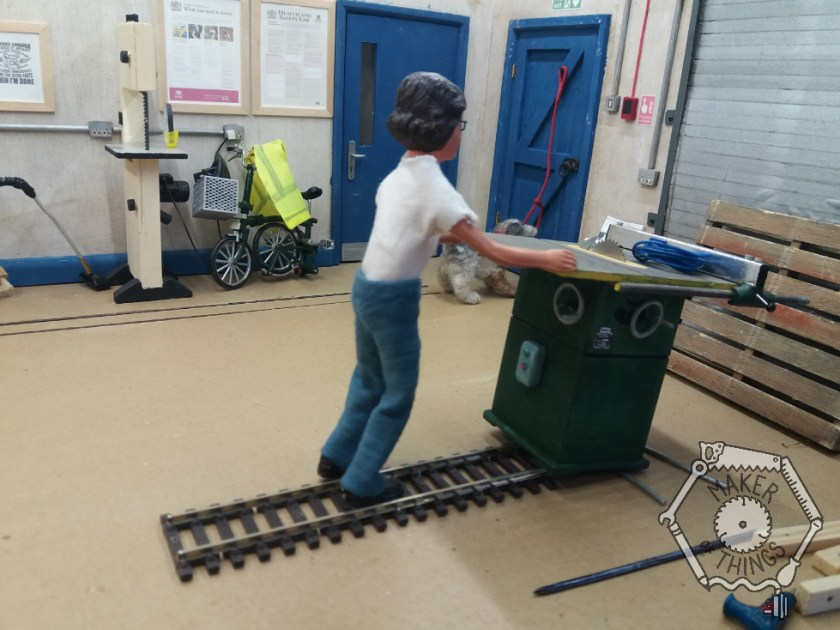 Harriet is easing the table saw onto the steel conduit tubes at the end of the railway track.