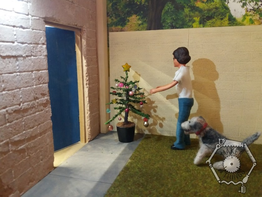 Harriet and Monty Dog are outside the workshop admiring their normal sized Christmas tree with its baubles on, and a star on the top.