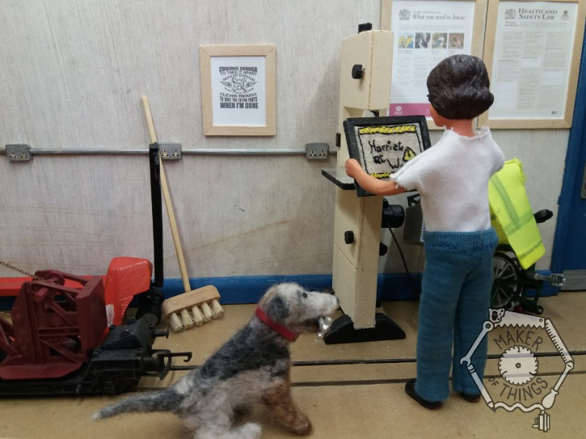 Harriet is standing at her bandsaw holding the framed embroidery. Monty Dog has a hammer in his mouth.