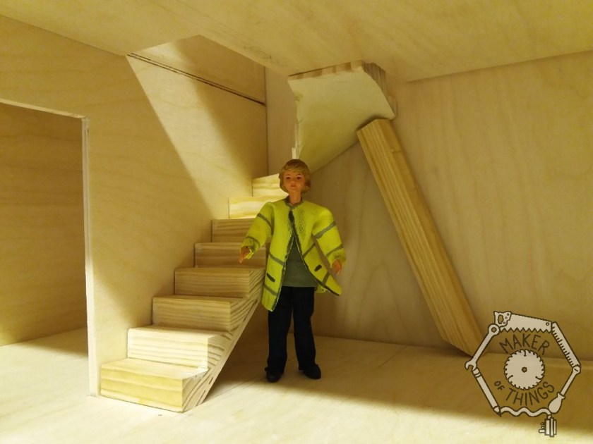 A 1:12 scale doll standing at a scale 5 feet 9 inches (or 175cm), standing next to the stairs for checking the scale.