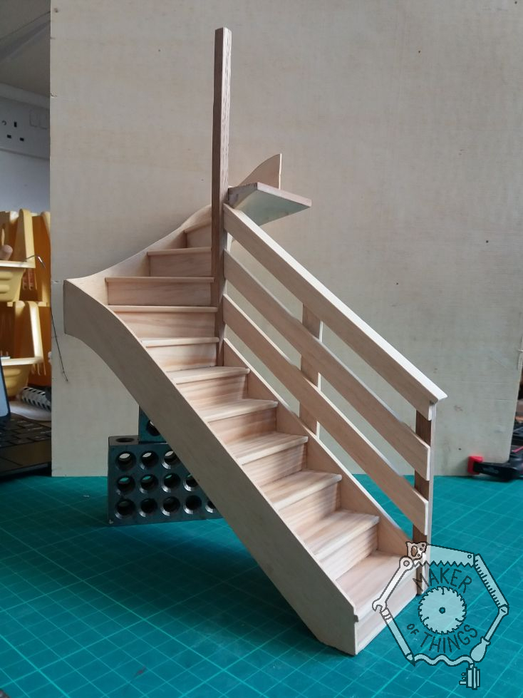 Wall side view of the staircase with hand rail fitted. A simple 1970s style of three 'horizontal' boards following the slope of the stairs.