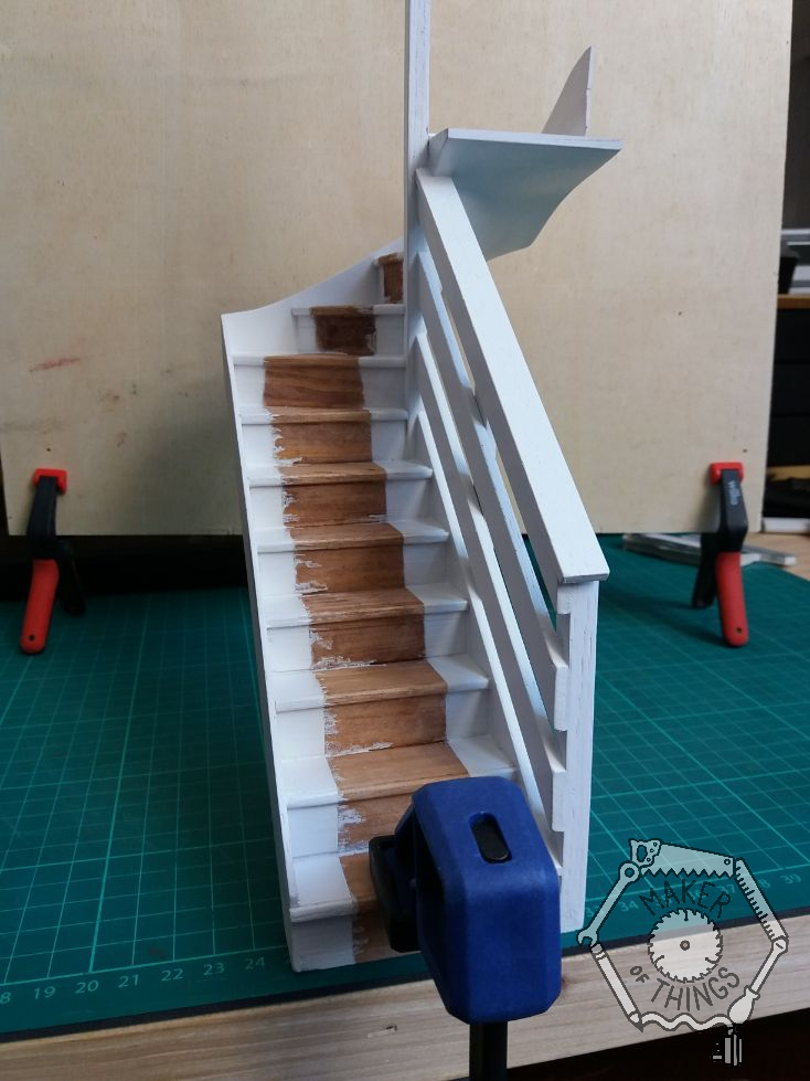 Front view of the staircase painted white leaving a bare wood strip where the stair carpet would be.