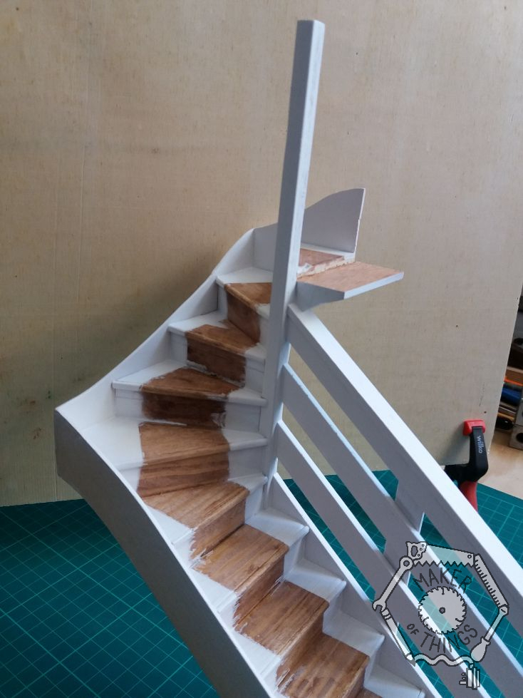 Wall side view of the staircase painted white leaving a bare wood strip where the stair carpet would be.