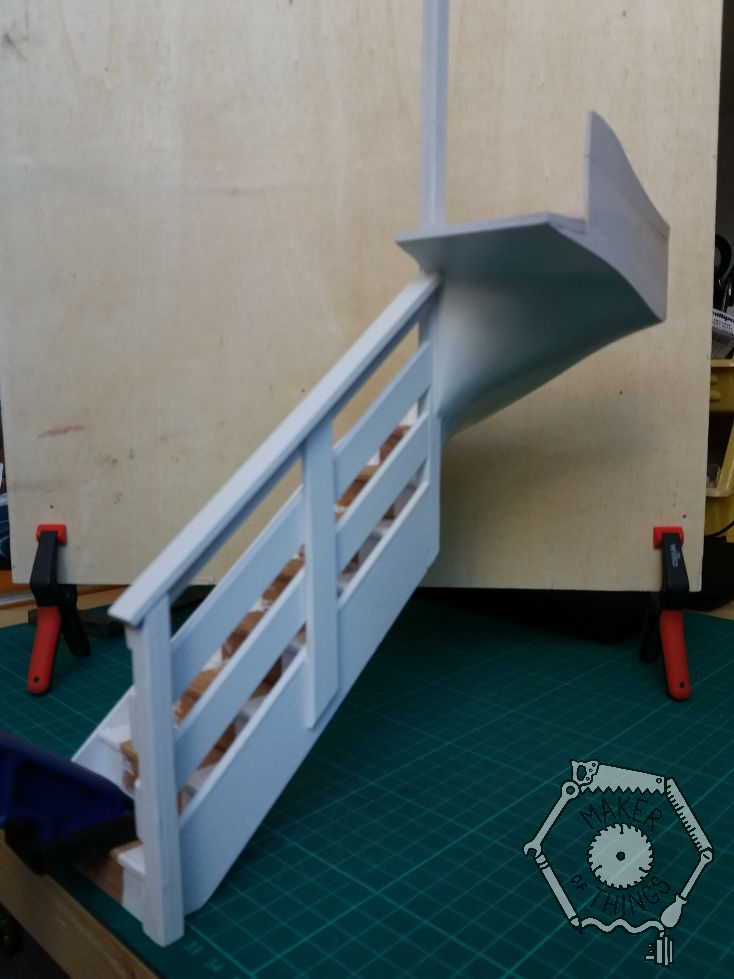 Room side view of the staircase painted white leaving a bare wood strip where the stair carpet would be.