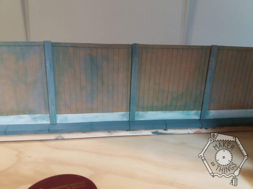 The fence panels in place with some dry brushed grey and green colours added.