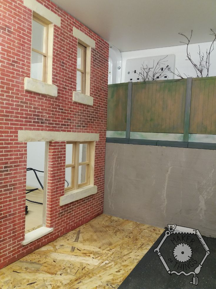 The house front placed on the backdrop against the concrete wall and fencing above.