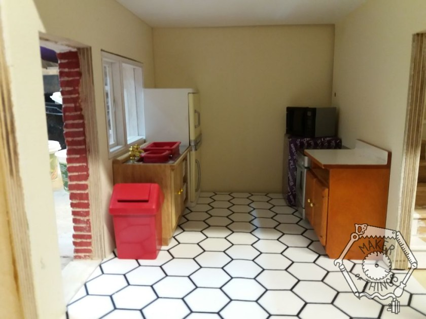 The kitchen showing the white hexagon flooring in place, and the furniture and appliances in position.