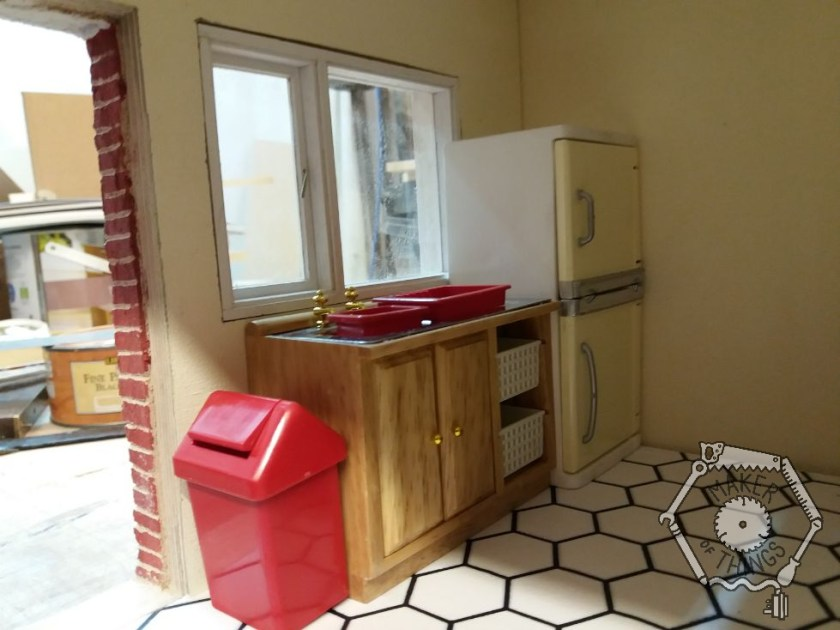 The kitchen showing the window, a red swing bin, the sink unit, and the fridge freezer. The fridge is overlapping the window due to its size.