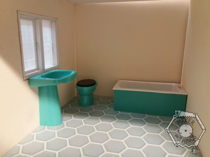 The bathroom showing the teal hexagon flooring, a blue basin under the window, a blue toilet in the corner, and a white bath with a matching blue bath panel.