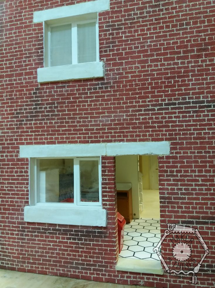 The back of the house with windows in place, the lintels and sills painted white, and a view through the back door and kitchen window showing the white hexagon flooring and the kitchen furniture and fridge,