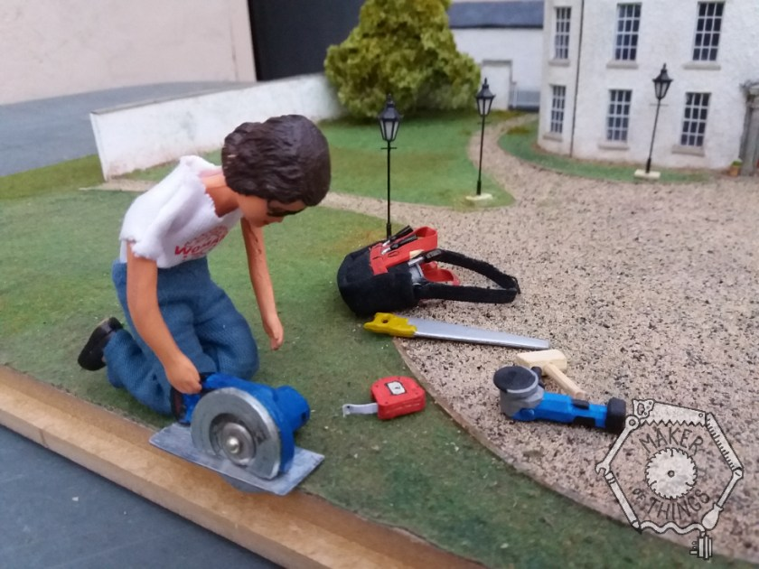 Harriet is kneeling on the grass at the edge of the plinth and is pushing her circular saw though the wooden edge.