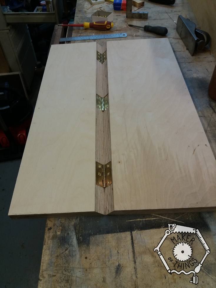 Two 18mm plywood boards lying flat on the bench with a 45⁰ mitre joint with three brass hinges holding them together.