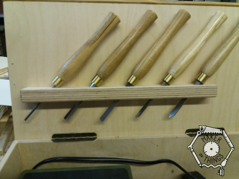 A close up of five chisels inserted into a wooden rail mounted inside the box lid. The chisels are slanted over at 45⁰ to fit within the width of the kid.