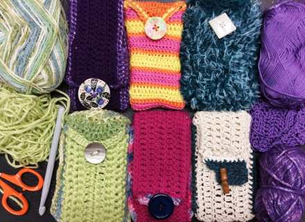 Crocheted mobile phone covers with decorative buttons, yarn, crochet hook, scissors.