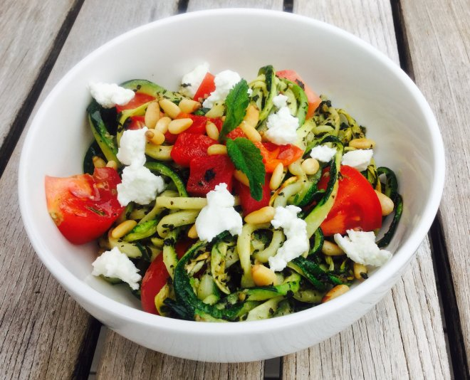White bowl with zucchini noodles, lemon balm pesto, roasted peppers and fresh tomatoes, topped with goat cheese and pine nuts