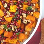 Roasted Squash with Hazelnuts and Pomegranate on a white plate with a wood serving spoon