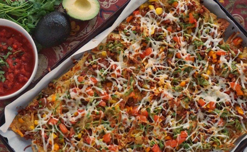Tray of nachos with lentils and avocado, bowl of salsa, avocado