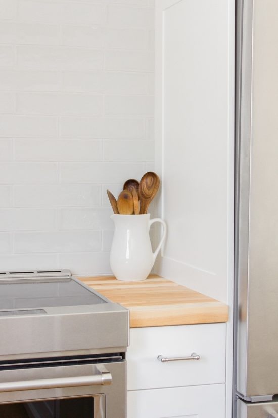 Wood spoons in white pitcher
