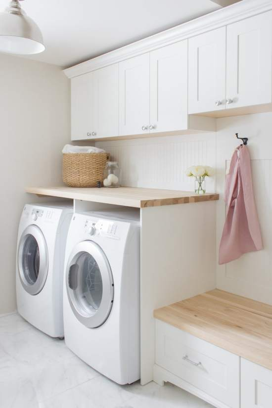 farmhouse laundry room with white cabinets
