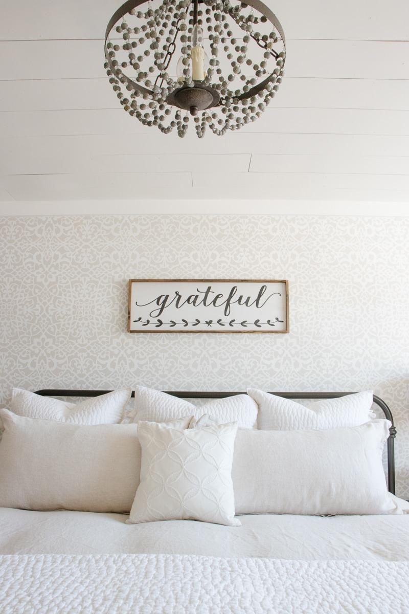 shiplap ceiling, beaded chandelier, linen bedding, stencil wall, wood sign