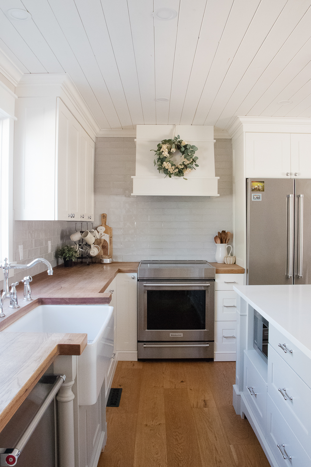 white kitchen cabinets, grey subway tile, wood counters