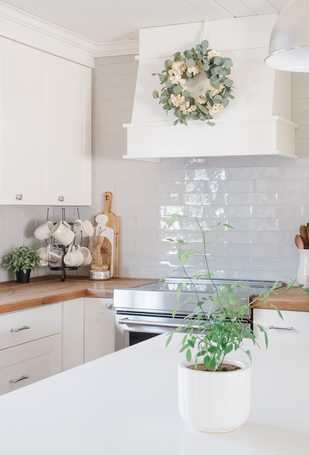 white kitchen, butcher block, wood range hood, wreath on range hood