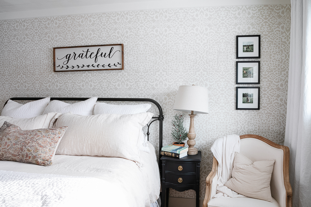 book stack, wood lamp, iron bed, black night table, wallpaper, stencilled wall, linen bedding, iron bed