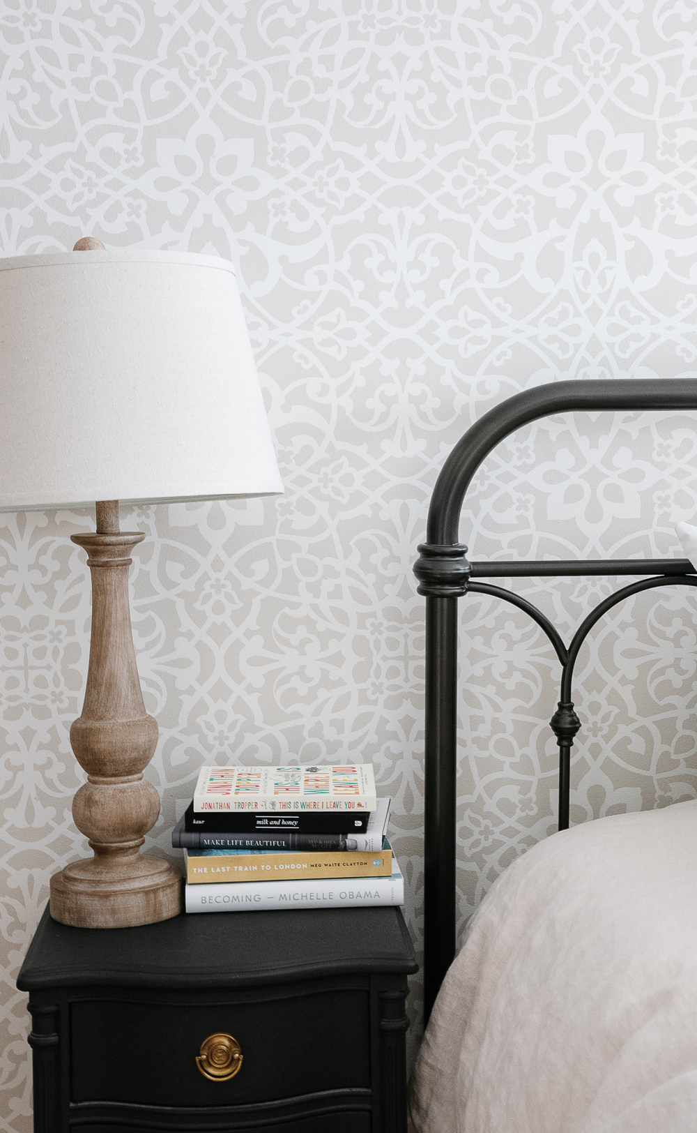 book stack, wood lamp, iron bed, black night table, wallpaper, stencilled wall