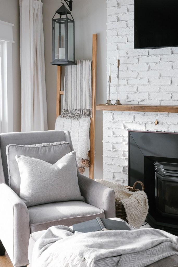grey chair, grey ottoman, blanket ladder, knit blanket, book