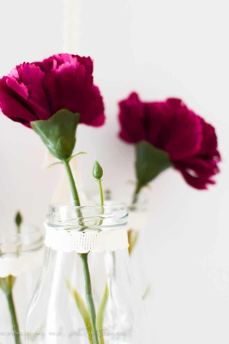 An easy farmhouse style DIY using milk jars and single stem flowers to make DIY hanging glass jars