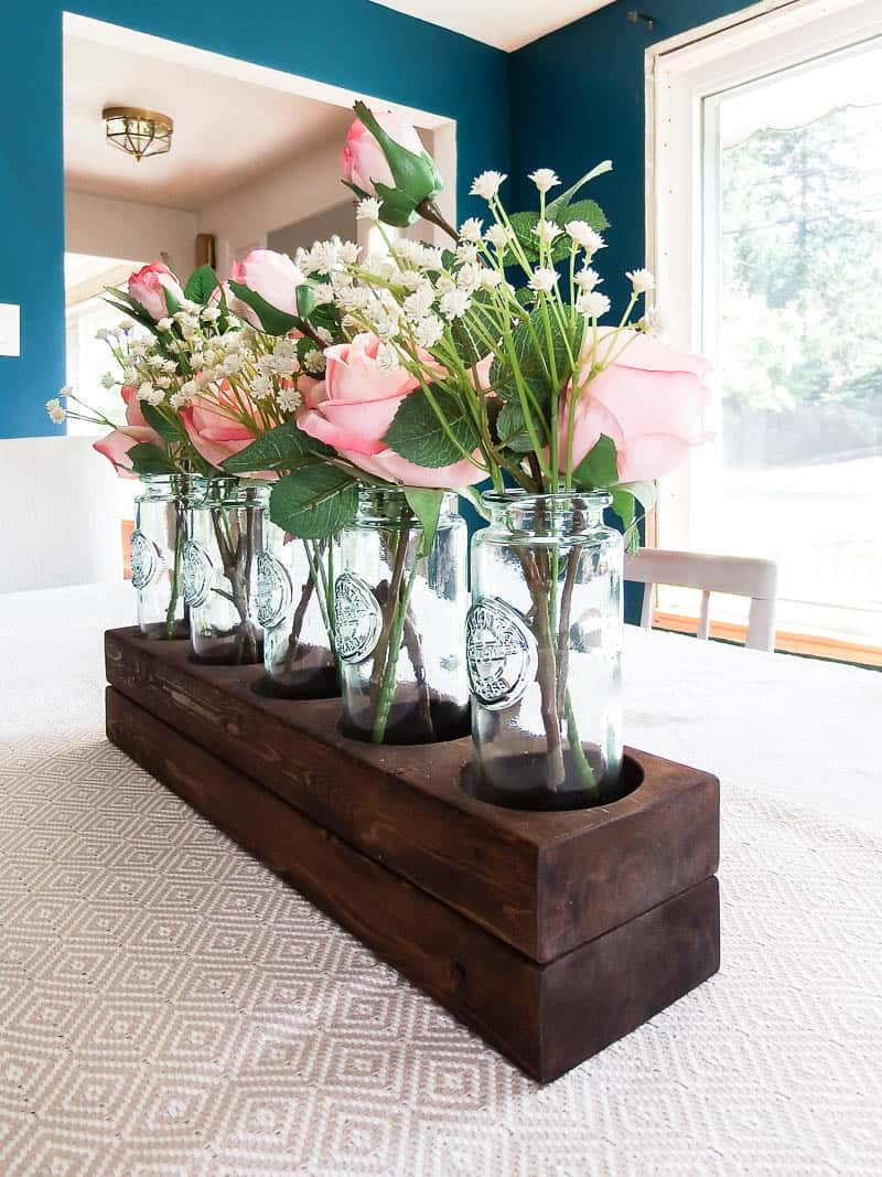 See how I used a scrap 2x4 board and transformed it into a simple wooden farmhouse style centerpiece using 5 blue glass vases.  Add in some beautiful silk roses and you have a gorgeous, easy centerpiece!