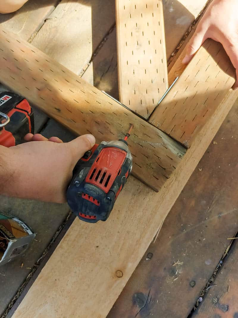 Man attaching additional wood diagonally in the middle of the rectangle frame for wooden gate using drill and deck screw