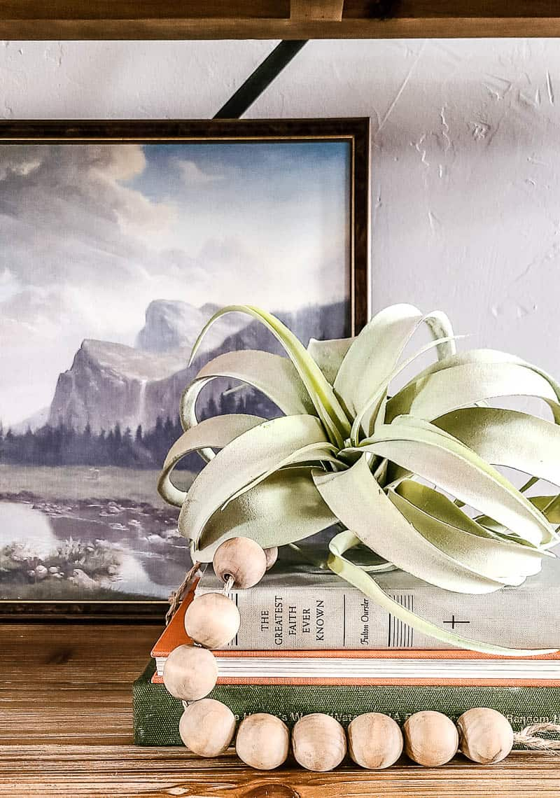 Large faux airplant with wood bead garland stacked on vintage books for shelf decor with vintage painting in background