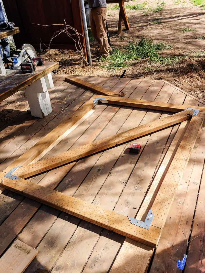 Wooden gate frame with cross brace laying on wooden porch floor before being installed on a fence