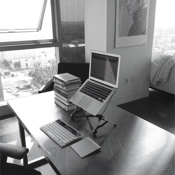 minimal desk setup with books and stand