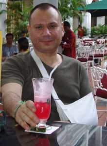 John Malathronas in the Raffles Hotel Singapore with a sling, drinking a Singapore Sling.