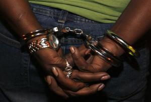 A woman who had an arrest warrant for possession of crack cocaine is handcuffed in South Los Angeles in this November 12, 2008 file photo.  REUTERS/Lucy Nicholson/Files