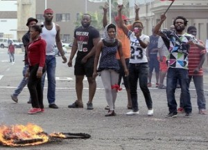 Foreign nationals gesture after clashes broke out in Durban's