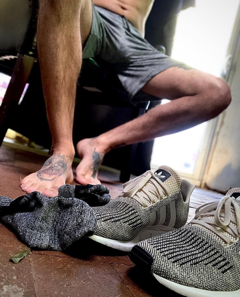 Xmr_phoenixx's tattooed bare feet out of socks and Adidas sneakers