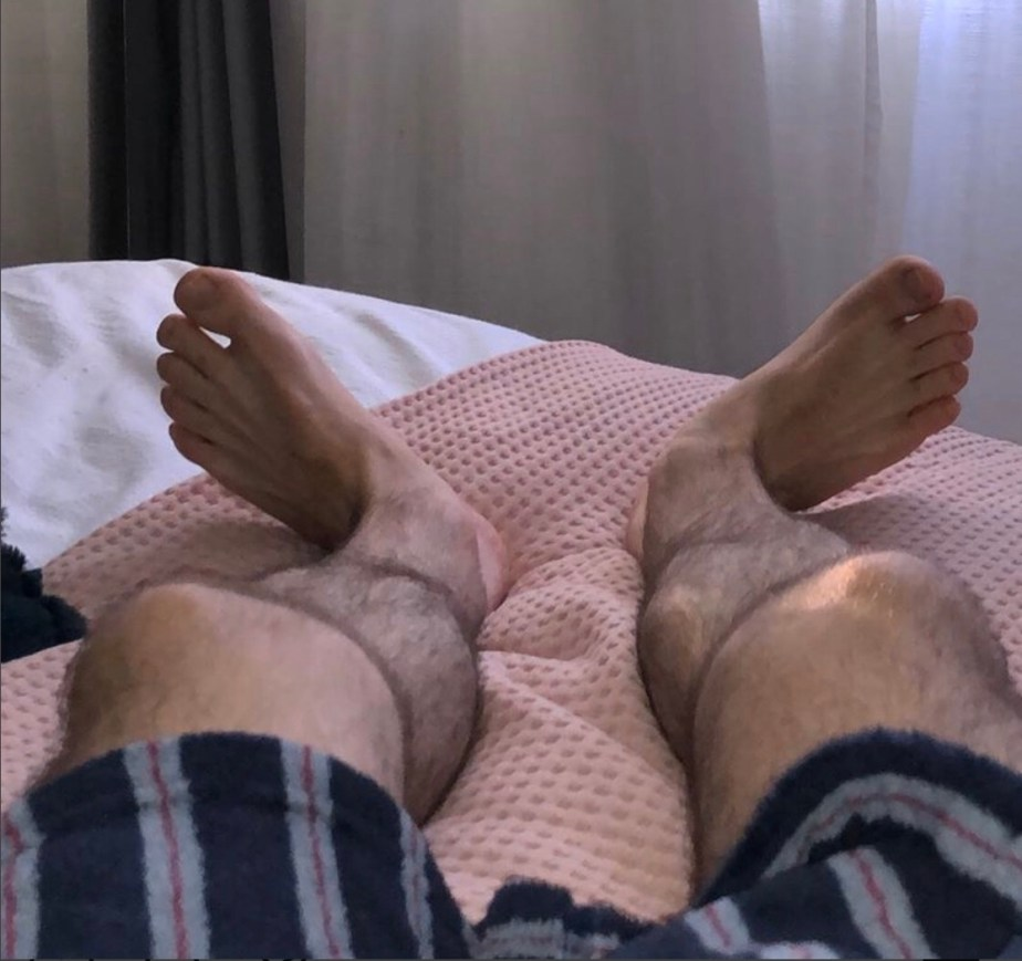 Jhollings2017 shows off his bare feet on the bed