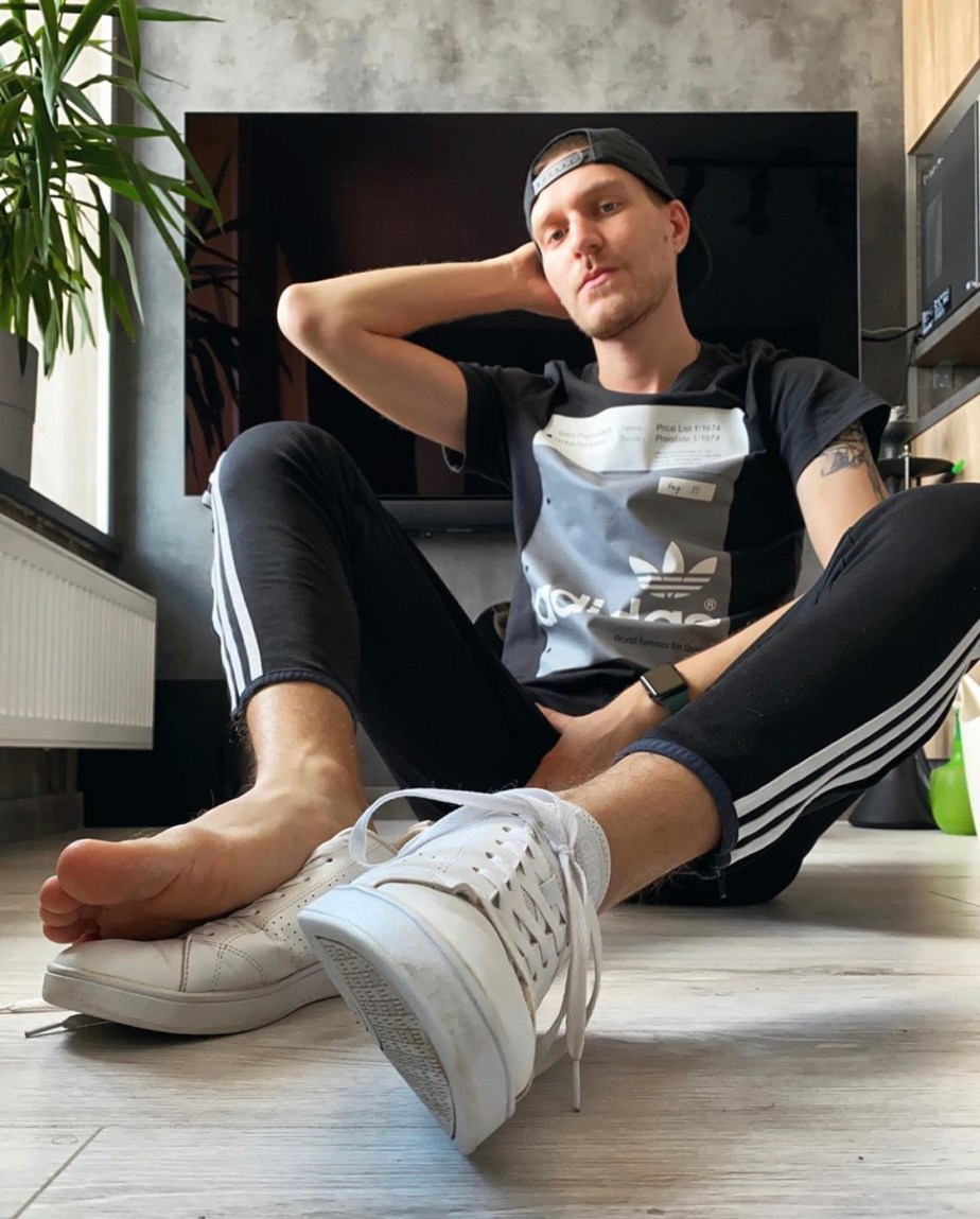 Stripsport shows off his bare foot out of his white Adidas sneakers