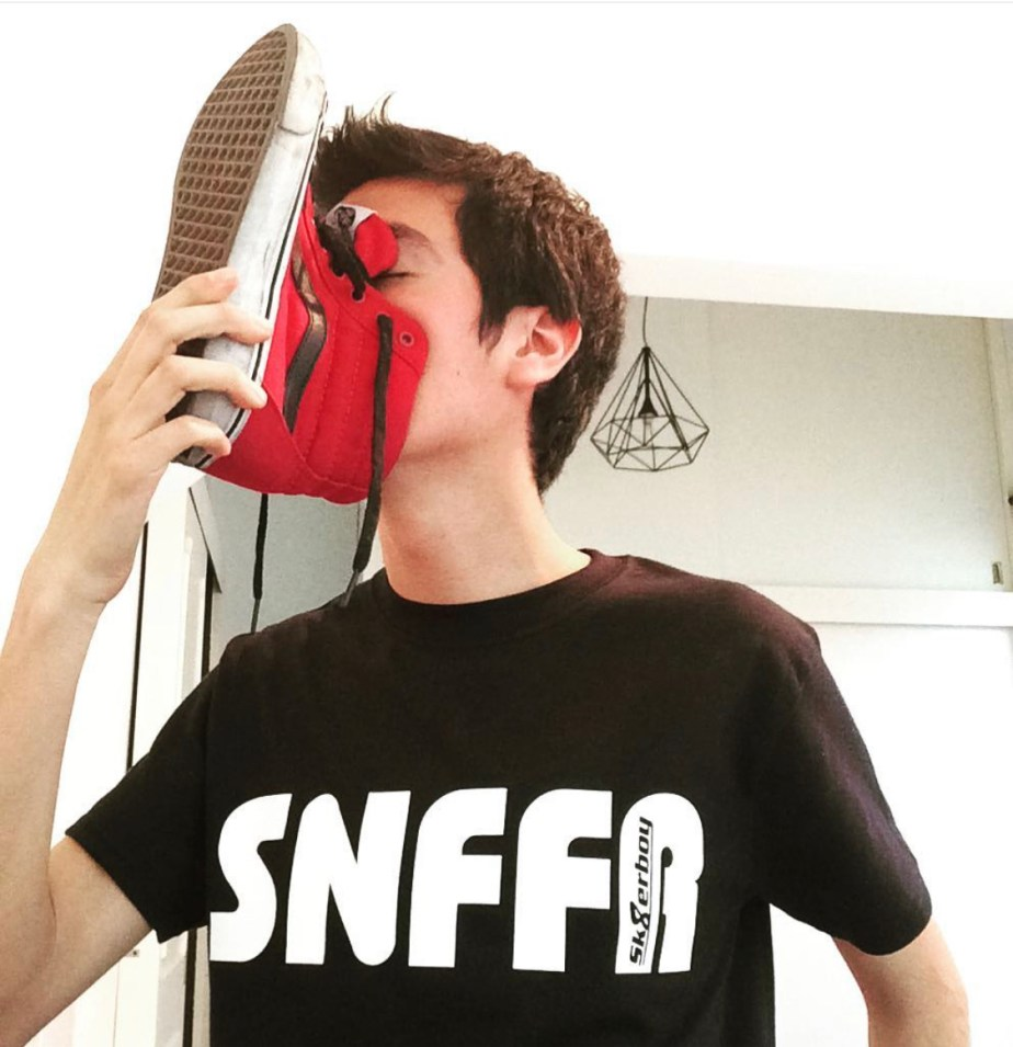 Snffrboy sniffing his red high top sneakers